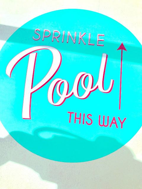 A sign that signals the way to the sprinkle pool