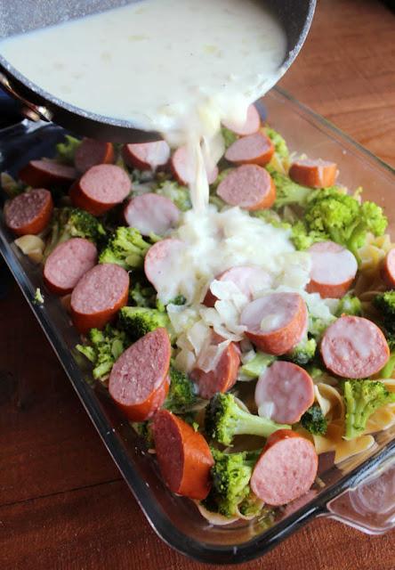pouring gravy mixture over pasta, kielbasa and broccoli in casserole dish