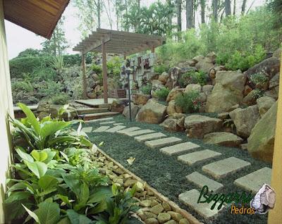 Pedra moledo para execução de paisagismo com o muro de pedra rústico com nichos para colocação de plantas e o caminho com pedra folheta.