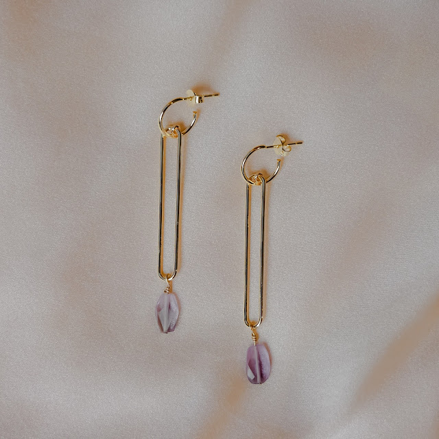 A pair of gold drop earrings with a purple gemstone as centerpiece.