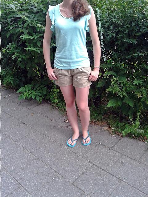 Miętowa bluzka z falbanami, beżowe krótkie spodenki, mini torebka, japonki z cekinami, bransoletka z kotwicą