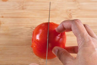 Slicing a tomato in half