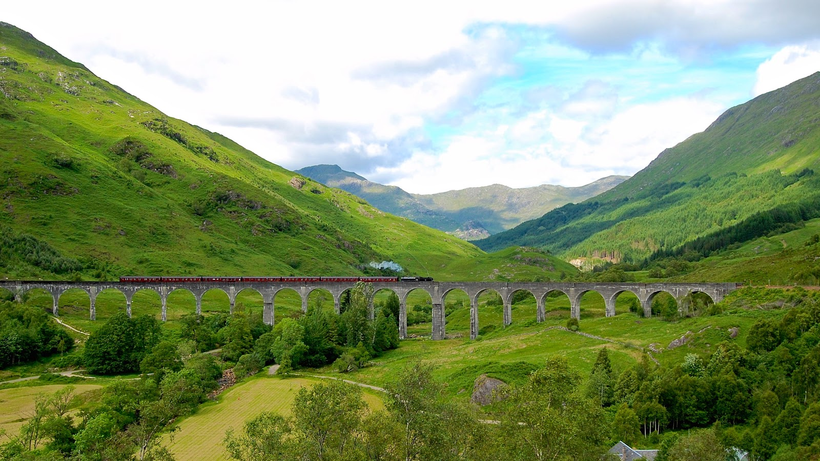 Jacobite steam train puffs across the Glenfinnan Viaduct in western Scotland