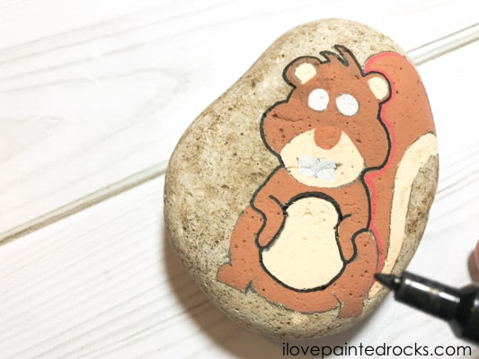 outlining the squirrel rock stone with a black posca pen