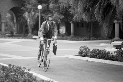 Don Kennedy riding a bike while carrying a briefcase