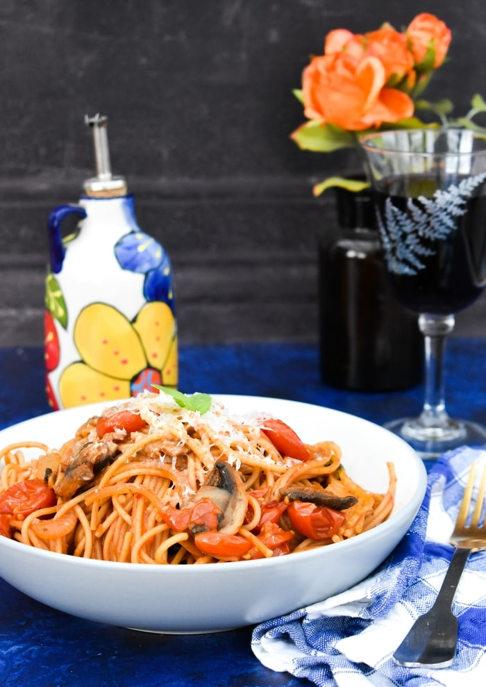 A bowl of spaghetti on a table with wine and flowers