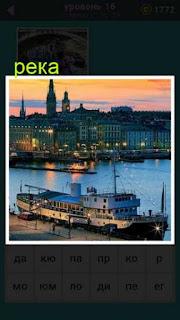 на фоне реки показан вечерний городи около пирса стоит корабль