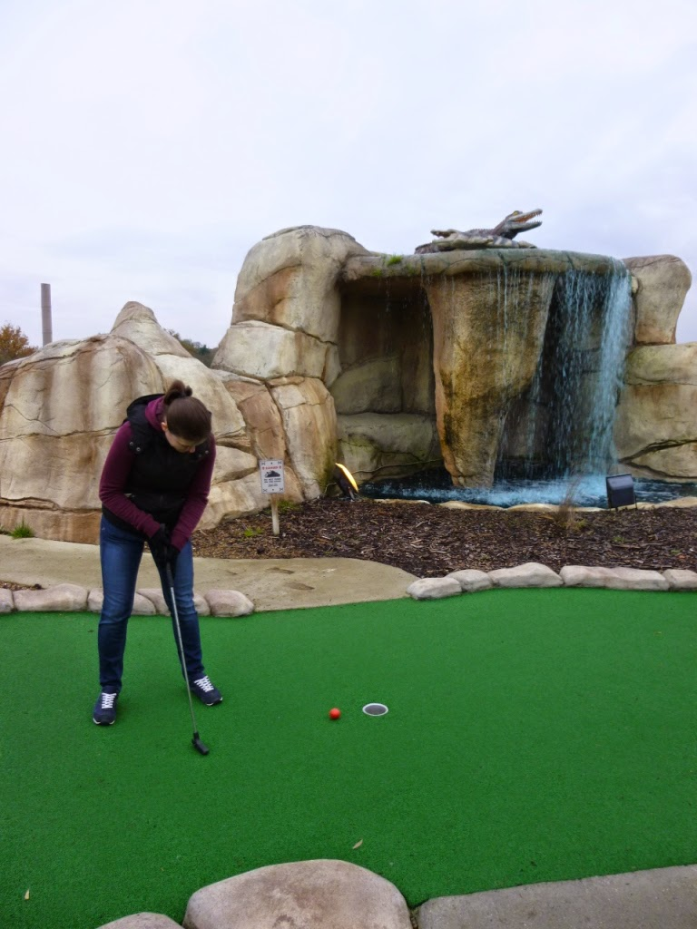 Emily putts as a couple of alligators, or crocodiles, look on at the Jungle Island Adventure Golf course at Horton Park Golf Club in Epsom, Surrey