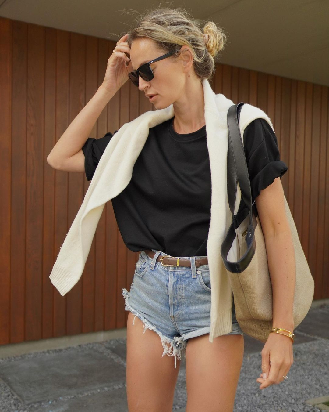 How to wear super short denim shorts — Anouk Yve transitional summer to fall outfit idea with black t-shirt, tote bag, and cutoffs