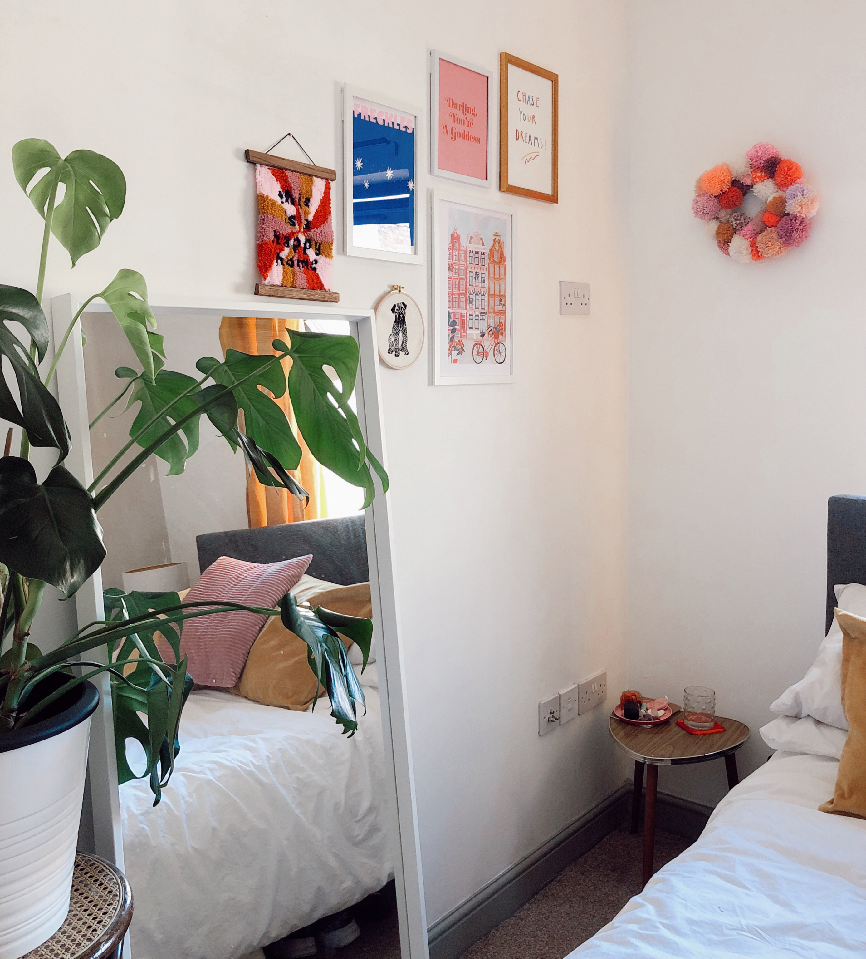 white corner of bedroom with monstera plant, large mirror leaning against wall, bed with white sheets, mustard and pink throw cushions and a small colourful gallery wall