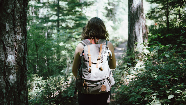 woman with a backback hiking in woods