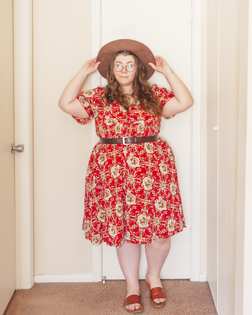 An outfit consisting of brown wide brim hat, a red short sleeve floral midi dress belted with a dark brown belt and brown slide sandals.