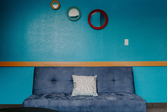 A cornflower blue couch in front of a turquoise-colored wall.