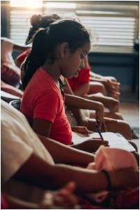 A girl taking notes in a classroom