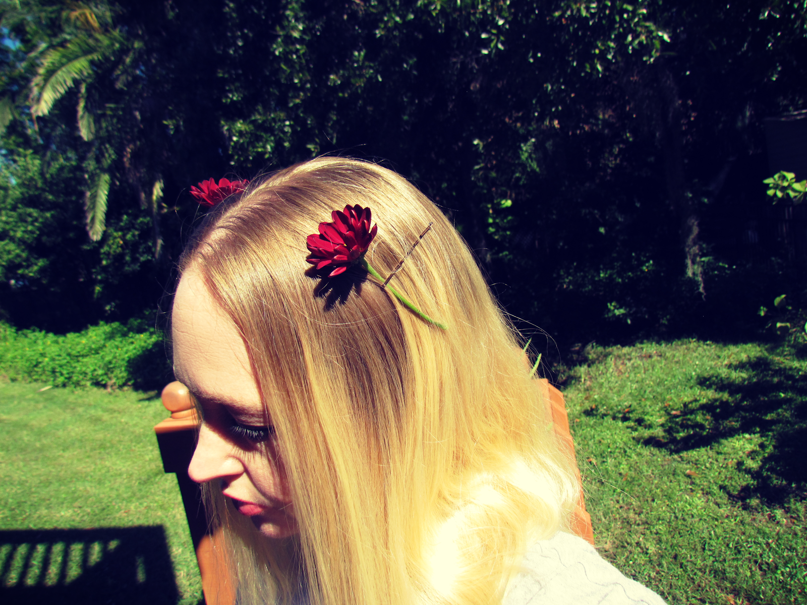 A woman wearing red living flower barrettes in her hair in a Florida landscape