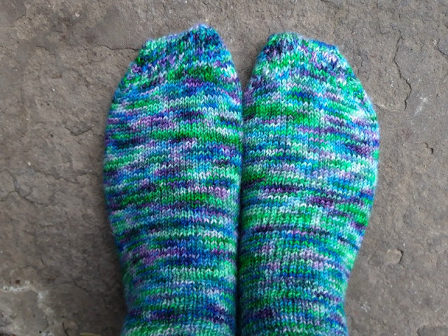 I'm standing on a stone paving flag wearing a pair of hand knitted socks in a green, purple and blue mottled yarn