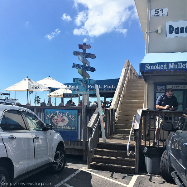 deck with tables, chairs, and umbrellas at the Olde Bay Cafe