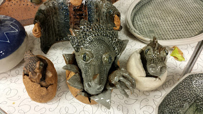 Assorted pottery by Lily L, with closeup on some dragon hatchlings.