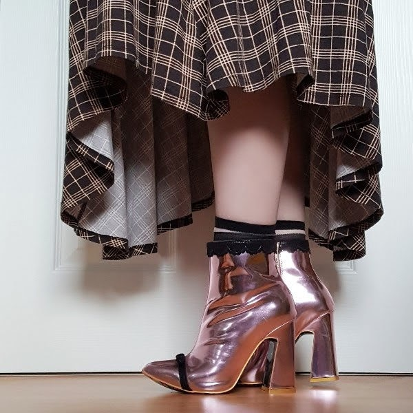 fashion blogger close up of legs wearing pink metallic ankle boots and checked dress