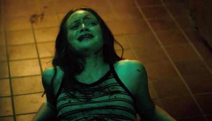 Imagem: a personagem de Sadie Sink, uma garota branca e ruiva, em uma camisa listrada, caída no chão de uma cozinha, coberta de sangue no rosto e no corpo, olhando para cima com um rosto machucado e assustado.