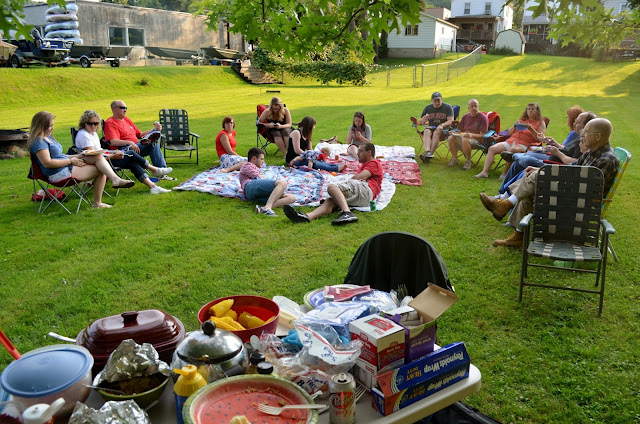 fourth of july picnic with big table of food and people sitting on blankets