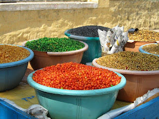 variety of colorful beans in bowls on a table outside