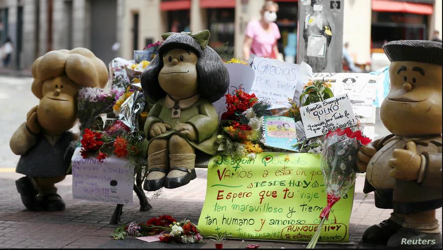 Flores y carteles rodean la escultura de los personajes de la tira cómica Mafalda, en Buenos Aires, tras la muerte de su creador, Quino. Octubre 1 de 2020 / REUTERS
