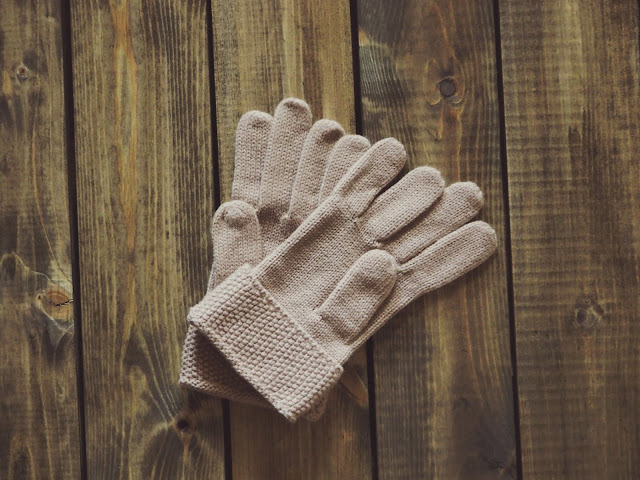Flat lay shot of a pair of gloves against a wooden surface.