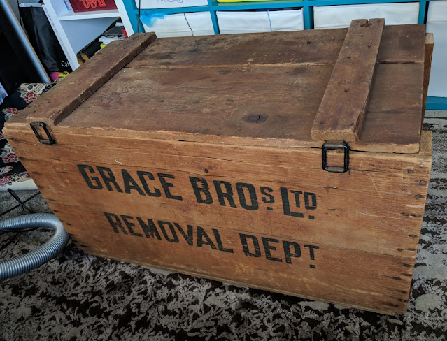 """A photo of a wooden crate with a lid, with the words """"Grace Bros Ltd Removal Dept"""" printed on the side."""