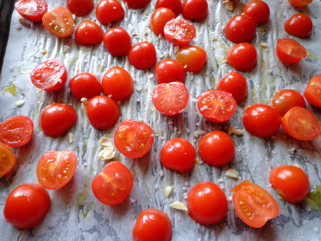 Place cherry tomato halves on a baking sheet
