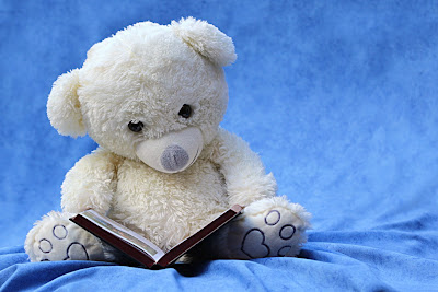 blue background with white teddy bear reading
