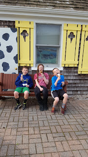 kids eating ice cream in front of ice cream parlor