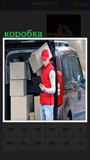 мужчина разгружает из машины коробки и читает накладную