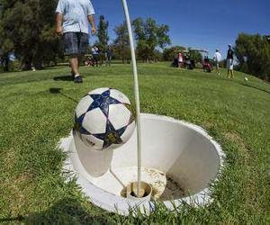 Football dropping into a footgolf hole