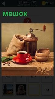 Чашка с кофе и мешок с зернами для кофемолки. Вокруг просыпаны зерна из мешка