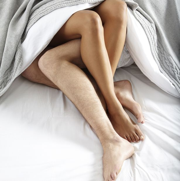 Close-up-of-couples-legs-in-bed-together