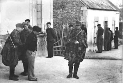 Three German soldiers are arresting a young man, handcuffing him. At least five more are lined up facing the buildings behind them.
