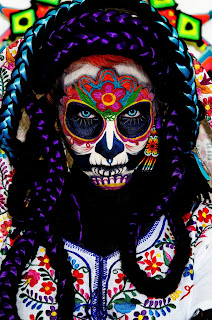 Close up of a woman white black and purple braids and an elaborately painted face. La Muerta by Fer Gomez on Unsplash.