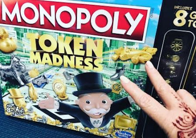 Cover of Monopoly Token Madness, with fingers showing to title