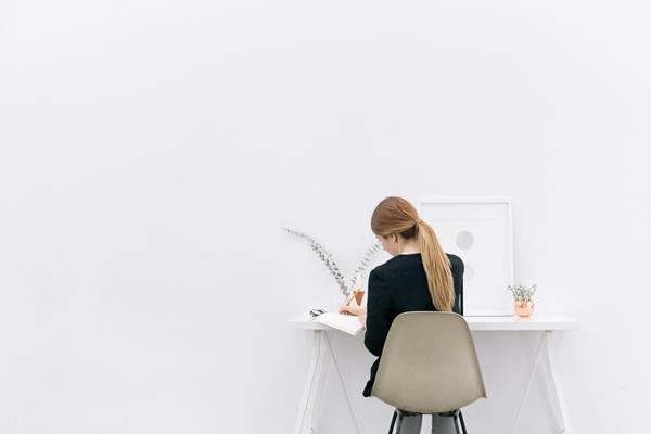Mulher sentada escrevendo de frente para uma parede branca