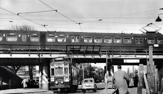 A monochrome image ca. 1954 of a train on an overhead rail bridge across the centre of the image, with electric cabling above it and a street below it, on the street are a tram and a car and a man walking away in the foreground.