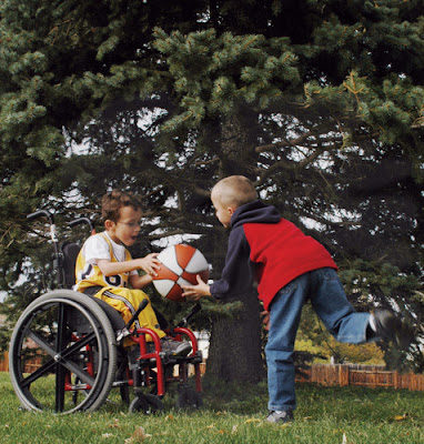 A picture of two boys, playing with a basketball in a yard. An able-bodied boy is on the right, wearing a red shirt, tossing the orange and white basketball to another boy using a manual wheelchair.