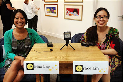 Alvina Ling and Grace Lin smiling into the camera while seated on opposite sides of a table with a recording device between them and their names on placards on table's edge