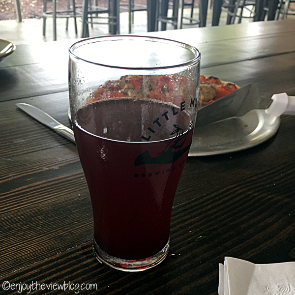 half glass of purple-red beer in a glass on a wooden table