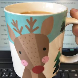 Rudolph mug in front of laptop