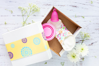 a gift box with menstrual cup, cloth pad, and cervical cup inside
