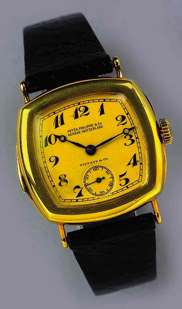 A color photograph of a Patek Philippe Swiss watch with a gold and yellow face, 1940s?