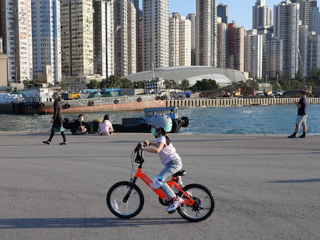 girl riding a bicycle while wearing a surgical mask and bike helmet
