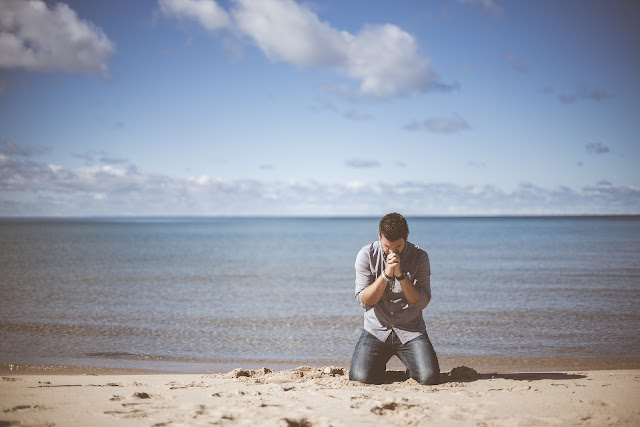 Man kneeling on beach begging to get his relationship back after his partner cheated on him
