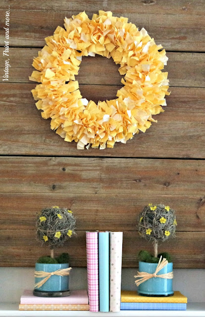 Fabric rag wreath and diy topiaries along with paper covered books for a pastel spring mantel